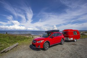 Red car and retro trailer, Vancouver Island, BC, Canada - May 10, 2018: Car camping with antique tiny trailer.