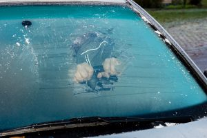 Removing ice from the frozen windshield