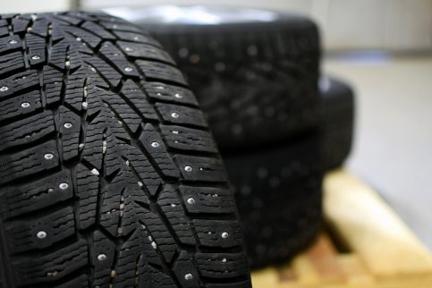 Snow tires with metal studs in garage. Small stones in the groove. Close up image, shallow depth of field.