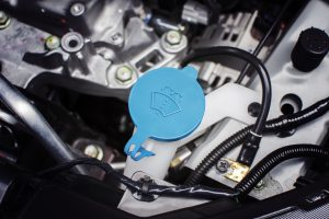 Windshield washer fluid cap with blue color in engine room of car, automotive part concept.