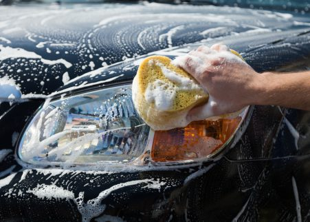 Man washing a soapy car with a yellow sponge.