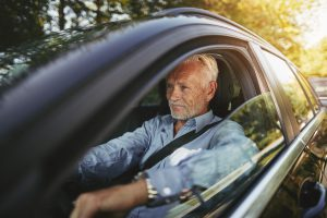 Senior man smiling while sitting alone in his car driving along a tree lined road in the country