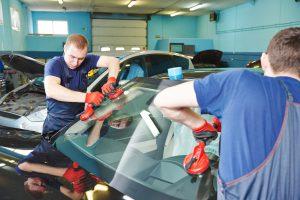Two men installing a windshield