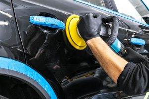 Car polish wax worker hands applying protective tape before polishing. Buffing and polishing car. Car detailing. Man holds a polisher in the hand and polishes the car