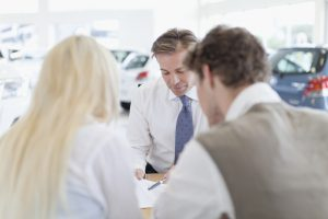Car salesman with customers at desk
