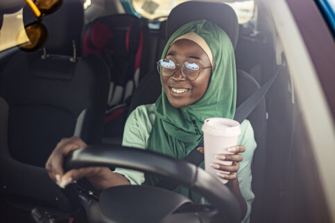 Teenager drinking coffee while driving