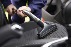 Vacuuming the interior of the vehicle.